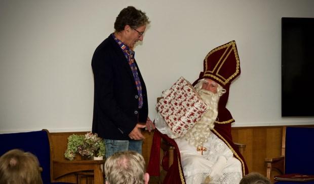 Samensteller van de tentoonstelling, Joop Tulp ontvangt van Sinterklaas een cadeautje.