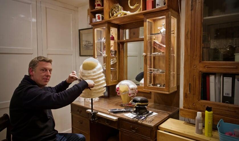 Mark in zijn atelier aan het onduleren van een baard.