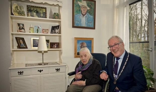 Mevrouw Hulsman samen met burgemeester Hans Romeyn bij een kast met de vele foto's en schilderijen geschilderd door meneer Hulsman.