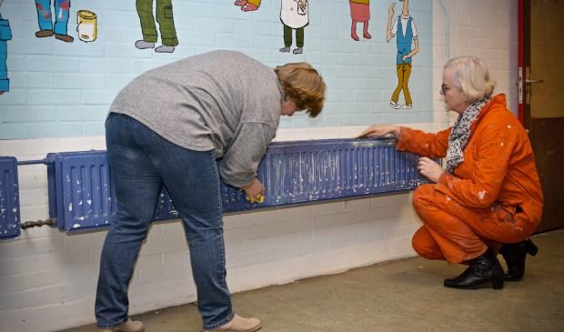 Gekleed in een oranje overall helpt wethouder Elly Beens tijdens NL Doet een handje.