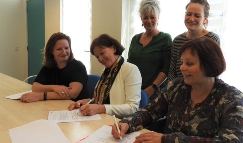 Directeuren Annemiek van de Vliet (de Duif) en Jeanette Braam (Bibliotheek Heiloo) ondertekenen het contract. Natasja Hoebe en Joke van Overbeeke (leescoördinatoren de Duif) en Marieke Ooijevaar (leesconsulent Bibliotheek) kijken toe.