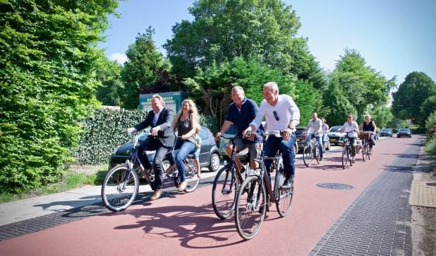 Wethouder Rob Opdam opent de fietsstraat door fietsend op de tandem de Hoogeweg op en neer te rijden. Achterop buurtbewoonster Wendy met zoontje Sky.