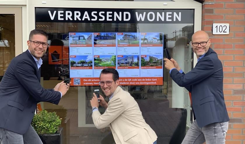 Bas, Jeffrey en Ronald nemen met hun eigen smartphone een 'virtueel kijkje' in en om de woningen via de flatscreen in de etalage.