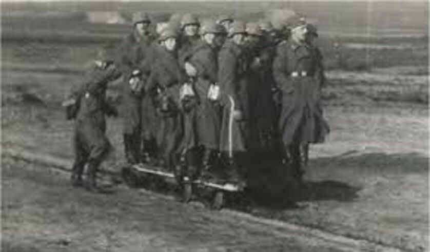 Duitse soldaten rijden mee met een platte lorrie.