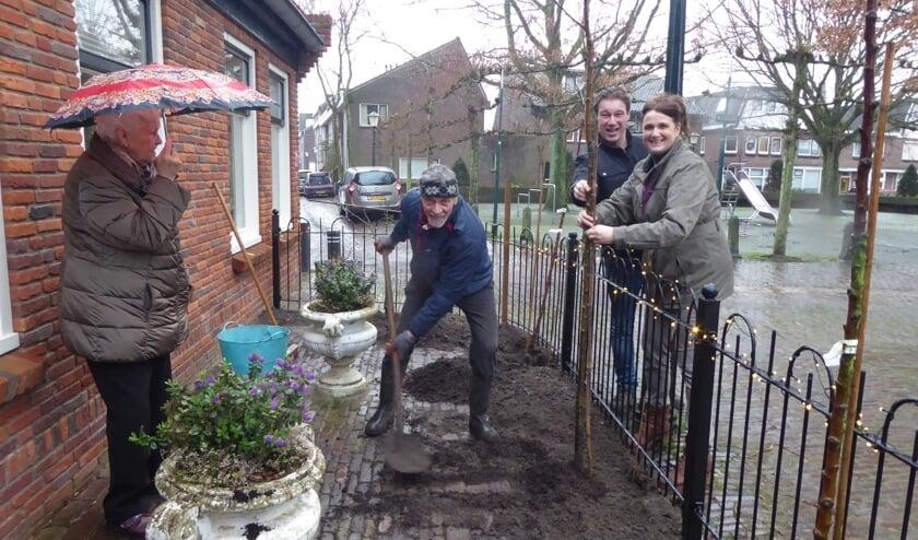Nico Brantjes plant boompjes in de voortuin  onder toeziend oog van Ilona en haar man Rob van Thuisbij.