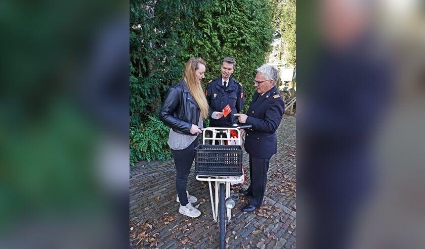 Martin Rensen (L) en Peter Weerd (R) overhandigen een cliënt van de voedselbank een fiets.