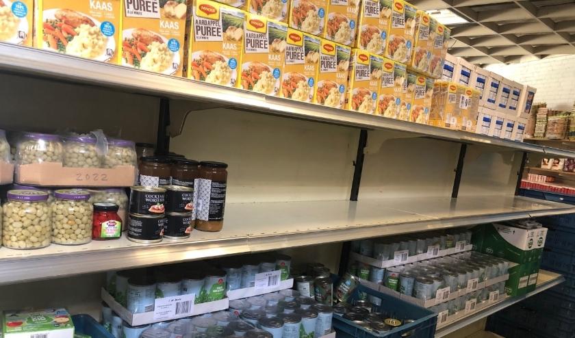Lege schappen in de loods van de Voedselbank.