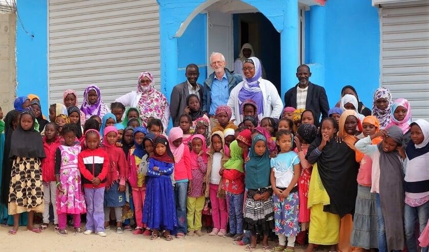 De school in betere tijden: Ad Corten samen met enkele onderwijzers en leerlingen voor een van de twee scholen van de Stichting SVM.