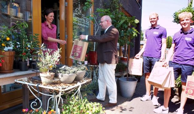 Wethouder Fred Dellemijn overhandigt het 'We zijn er voor elkaar' promotiepakket aan eigenaresse Kim van Bloemen bij Kim, Stationsplein 47 in Heiloo.