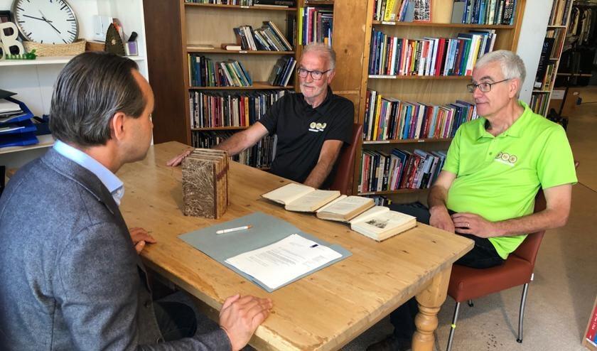 <p>Penningmeester George Tervoort (l) en Wim Maan (r) , vrijwilliger op de boekenafdeling van XopX tekenen de akte van schenking.</p>