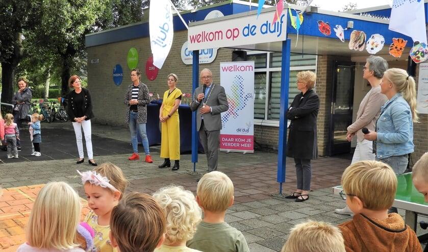 Burgemeester Romeyn opent kindcentrum De Duif samen met kinderen, directie, bestuurders, partners  en medewerkers tijdens het muzikale startfeest.