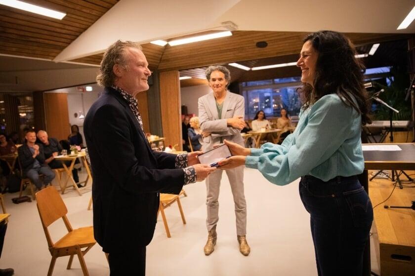 Wethouder Touria Meliani reikt de Koninklijke Onderscheiding uit aan Kees Scholten (links op de foto)