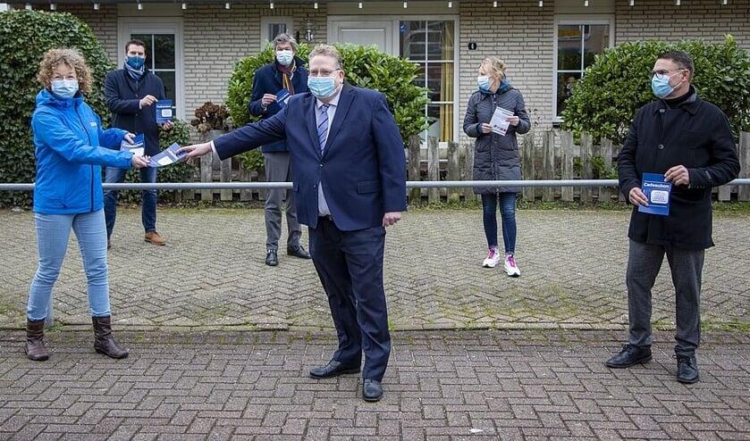 Overhandiging dinerbon door burgemeester Mans en wethouder Slettenhaar aan vertegenwoordigers Buurt- en Thuiszorgorganisaties.