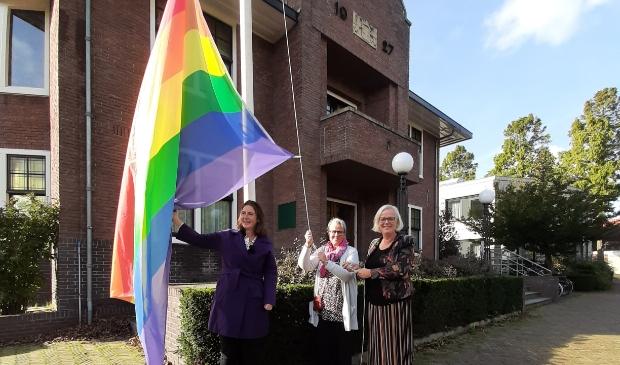 <p>Burgemeester Mascha ten Bruggencate, Dhyan Duijn en wethouder Elly Beens hijsen de regenboogvlag.</p>