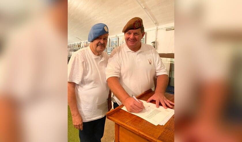 <p>Dannij van der Sluijs (rechts) en Hans Walrave ondertekenen de akte van oprichting bij de notaris.</p>