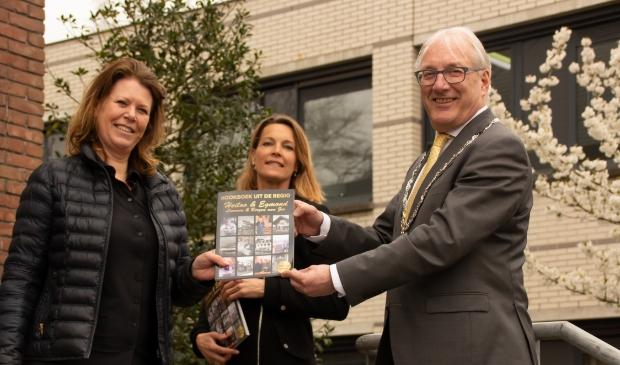 <p>Uitgever Sylvia Blok (l) en Judith Pronk (o.a. sponsorwerving) overhandigen een exemplaar aan burgemeester Romeyn. </p>