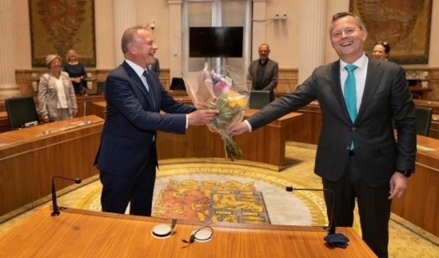 Commissaris van de Koning in Noord-Holland Arthur van Dijk overhandigt een welkomstbloemetje aan waarnemend burgemeester van Heemskerk K.S. Heldoorn (links).