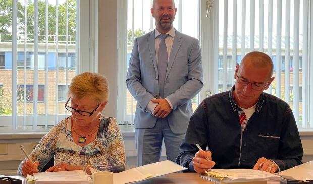 Christel en Siem Mol tekenen koopcontract in het bijzijn van burgemeester Nieuwland.