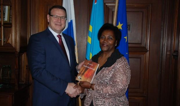 Irma Grovell overhandigt haar roman 'Glanzende Schoenen' aan de gevolmachtigde minister van Aruba, Alfonso Boekhoudt.