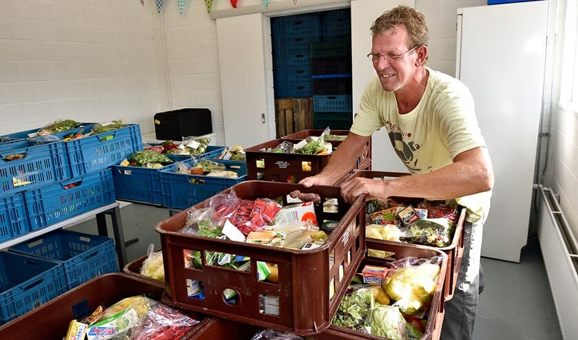 Vrijwilliger stelt voedselpakketten samen.