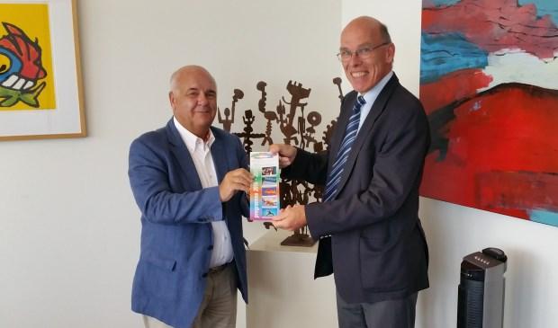 Huizer burgemeester Fons Hertog krijgt de eerste brochure uit handen van Evert de Jong, voorzitter Volksuniversiteit Het Gooi.