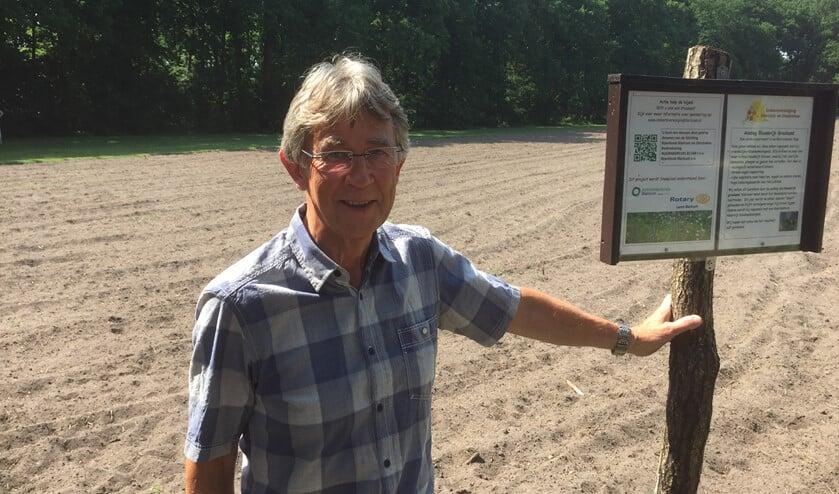 Piet Broeksteeg bij het bord met uitleg over het project op de akker die zal veranderen in bloemrijk grasland.