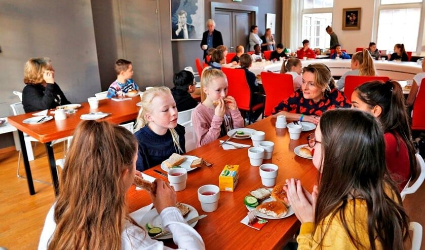 Wethouder Karin van Hunnik samen met de leerlingen aan de ontbijttafel.
