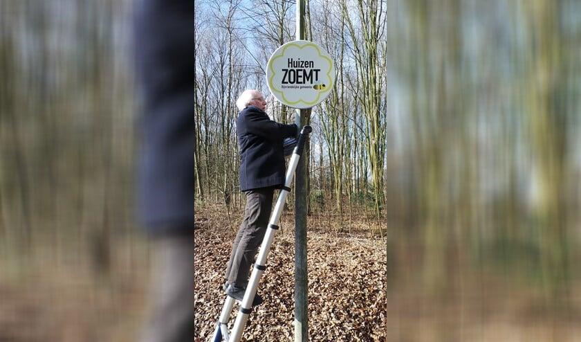Wethouder Gerrit Pas bevestigt het bord dat laat zien dat Huizen bijvriendelijk is.