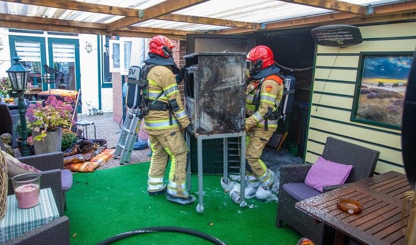 De brandweer draagt het verbrandde apparaat uit de schuur.