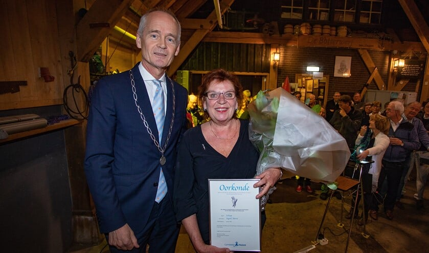 Burgemeester Niek Meijer met Ingrid Helmus-Schaap die het Huizer Insigne van hem kreeg opgespeld.