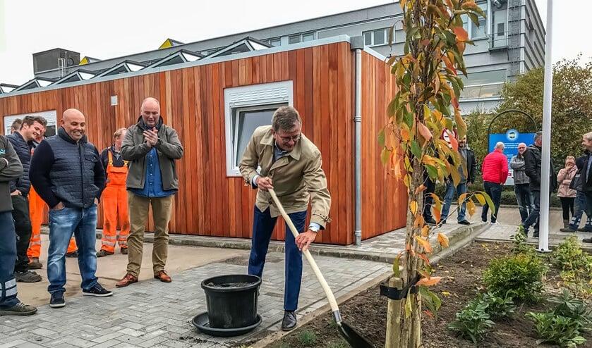 Wethouder Bert Rebel plant een Japanse kers als officiële opening van het gebouw.