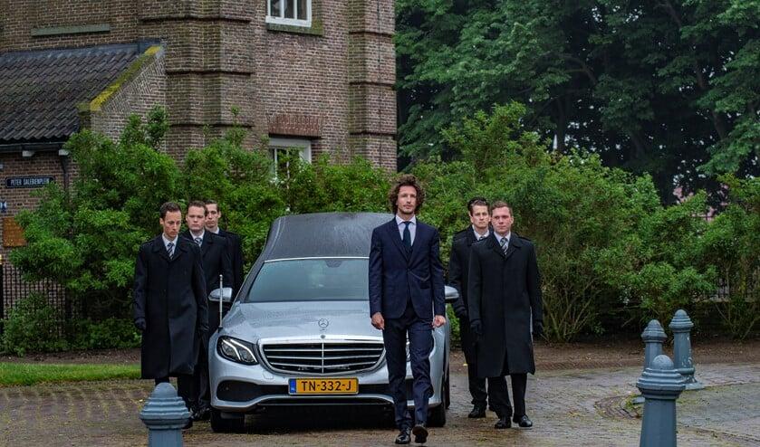Iede Hoorn (voor de auto) leidt een uitvaart.