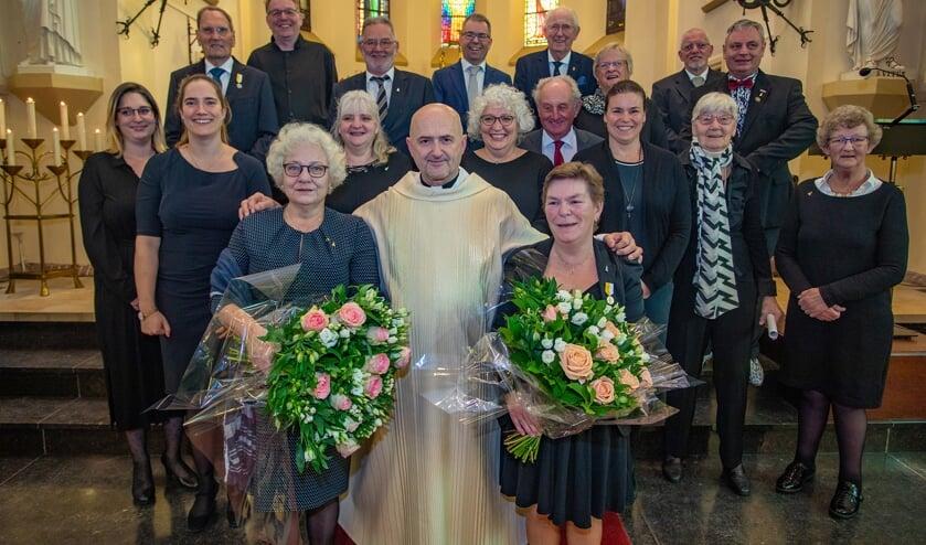 Bloemen en onderscheidingen voor twee koorleden.