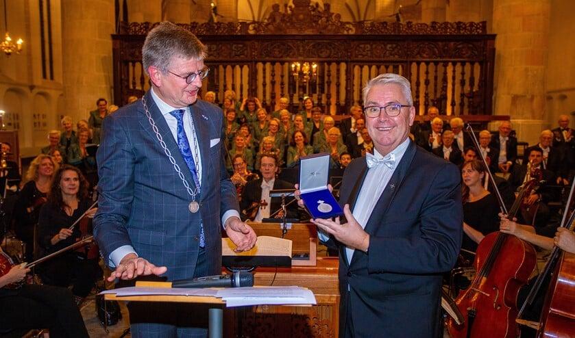 Loco-burgemeester Bert Rebel (l) overhandigde de penning aan zijn broer en de voorzitter van het koor, Eduard Rebel.