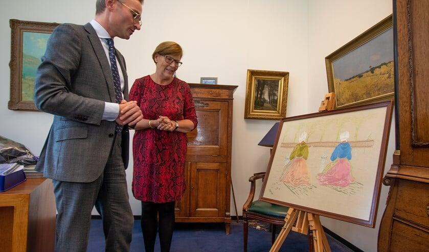 Nanning Mol en Joke de Groot-Stek kijken eens goed naar het borduurwerk van Lena de Jong.