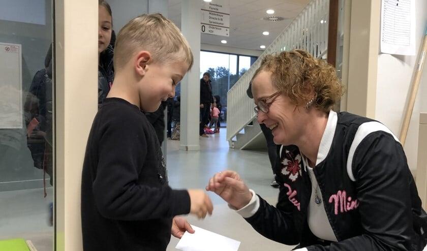 Levi geeft zijn kaartje aan juf Ied. Sam (op de achtergrond) heeft een kaartje voor juf Britt bij zich.