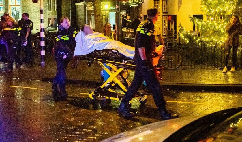 De gewonde agent wordt door collega's naar de ambulance gereden.