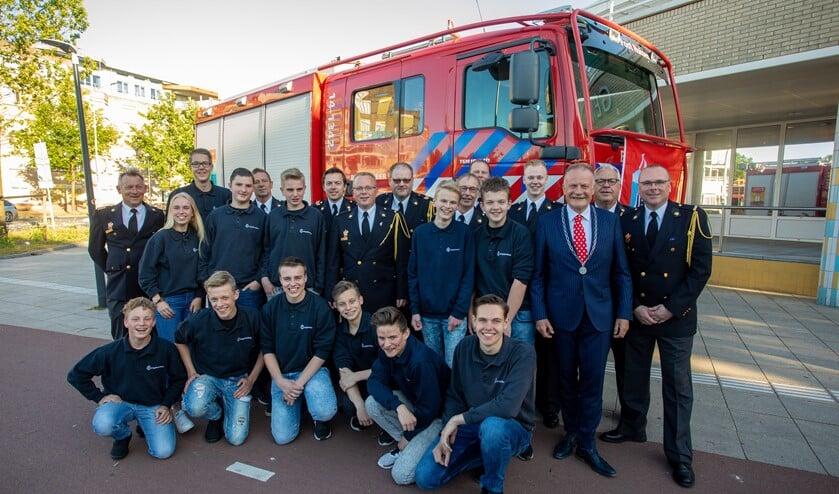 De jeugdbrandweer met begeleiding met links brandweercommandant John van der Zwan en rechts postcoördinator Fred Kos, geflankeerd door de burgemeester.