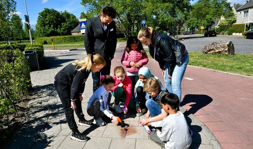 Leerlingen markeren een plek waar hondenpoep ligt.