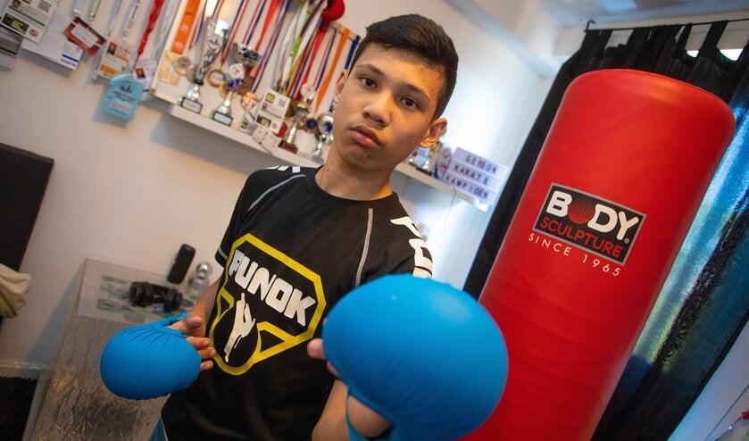 Gerson in zijn slaapkamer, waar hij ook kan trainen, met op de achtergrond al zijn behaalde prijzen.