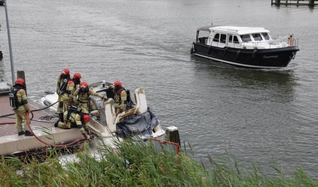 De brandweer druk bezig met het blussen van de brand op de motorboot.