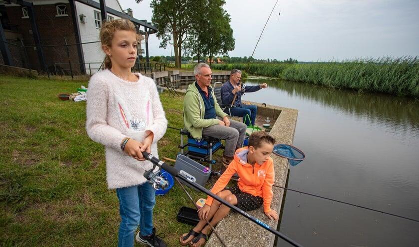Annelot en Marijn gaan vaak met hun vader Gerlof mee vissen, net als vriend Hans Kaarsgaren (r).