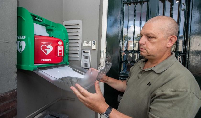 Ed Bakker toont de AED, die sinds vorige week bij De Geus hangt.