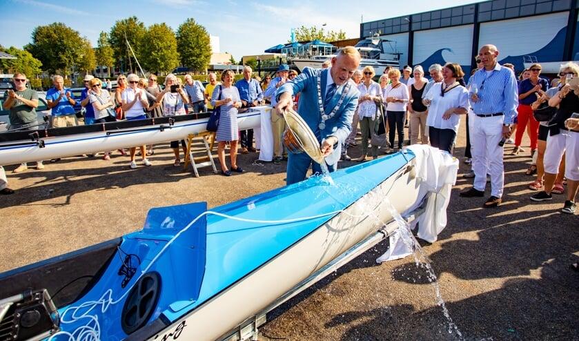 Burgemeester Han ter Heegde van Gooise Meren doopt de nieuwe roeiboot in Huizen.