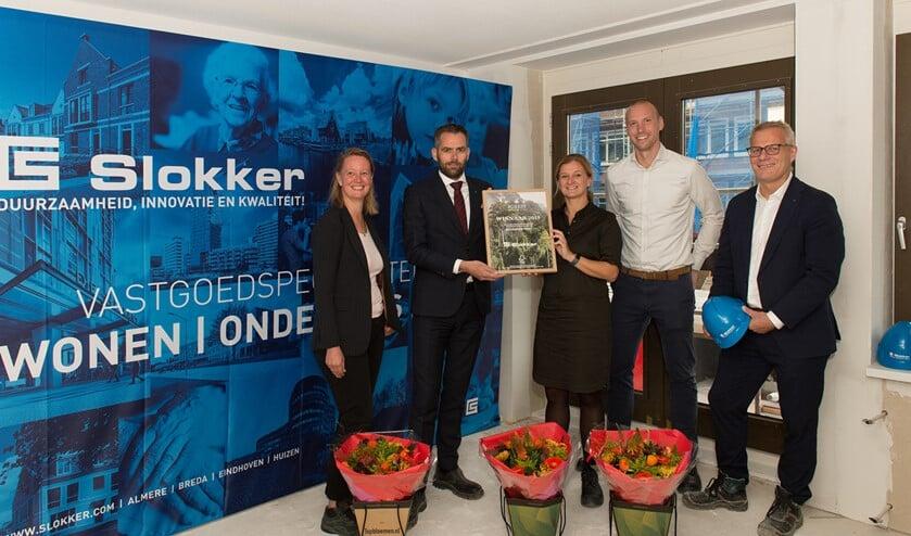 Stefan Wildhagen en Erna Snelder van Slokker nemen het certificaat en de bos bloemen in ontvangst uit handen van Liesbeth Gort, directeur FSC Nederland.