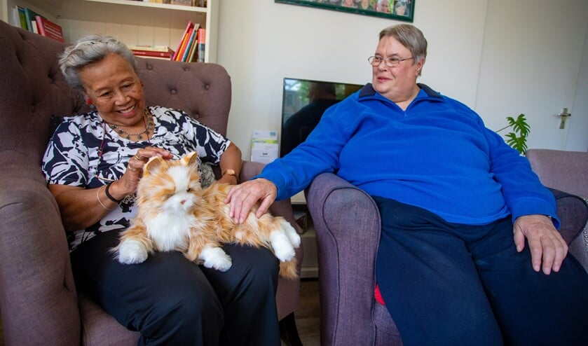 Erica (rechts) aait de robotkat die een lekker plekje heeft gevonden in het Geheugenhuis bij Trui op schoot.