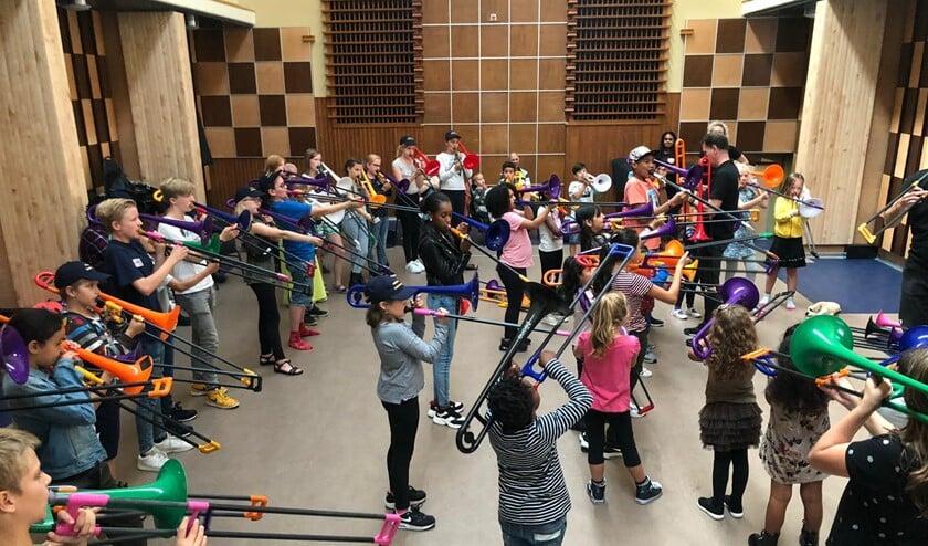 De kinderen speelden een muziekstuk op de trombone.