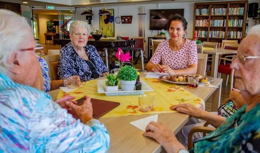 Initiatiefneemster Marian van den Berge aan tafel bij een aantal ouderen bij De Marke - De Meenthoek.