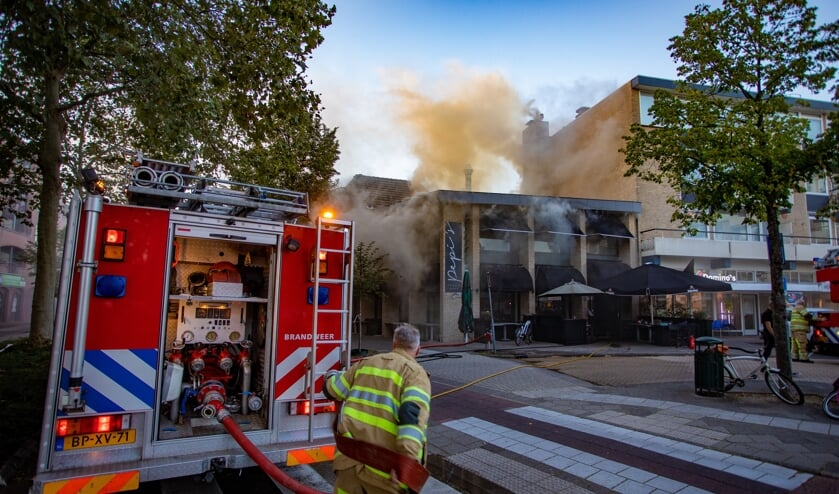 De brandweer druk bezig met de brand bij Pepi's.