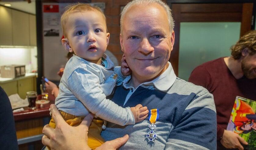 Hans Schotsman - hier samen met kleinzoon Loui - is trots op zijn onderscheiding.